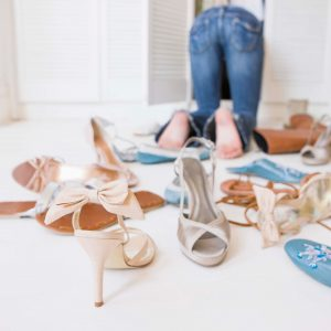 woman cleaning out closet with shoes everywhere for post 3 easy steps to break the hoarding habit