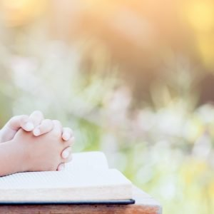 Hands resting on Bible, praying outside with text reading 5 Powerful Ways to Pray for Your Husband