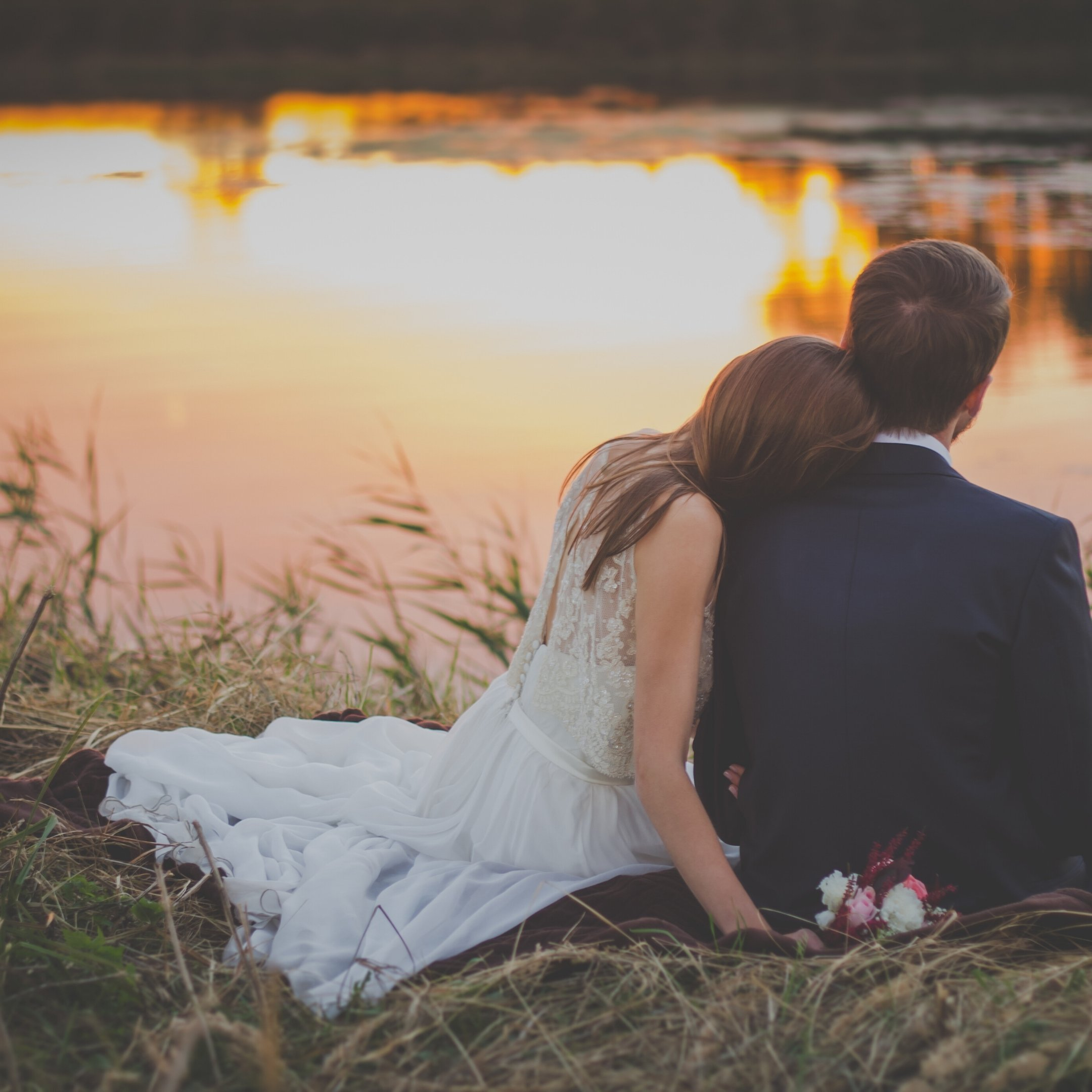 Bride and groom overlooking pond at sunset for post How to Be a Better Wife in 9 Easy Steps