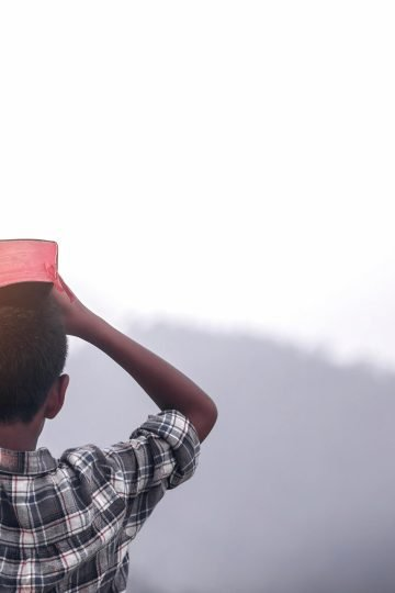 Boy outside holding Bible on his head for post how to do devotions with kids, specifically your tweens