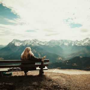 girl sitting on bench looking at mountain view for post perfect bible verses for when you need peace