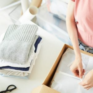 woman folding clothes for post what is a christian minimalist